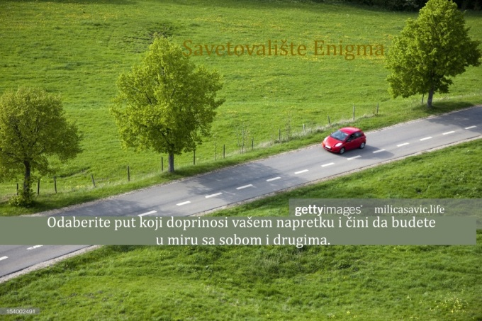 small red car driving down country road, springtime, elevated view,